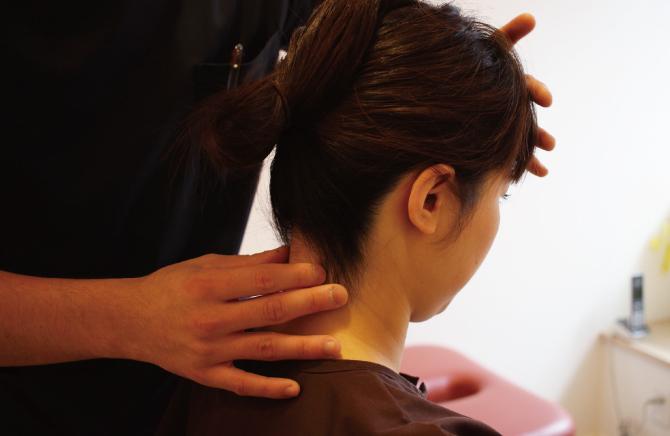 頸椎の触診検査をしている
