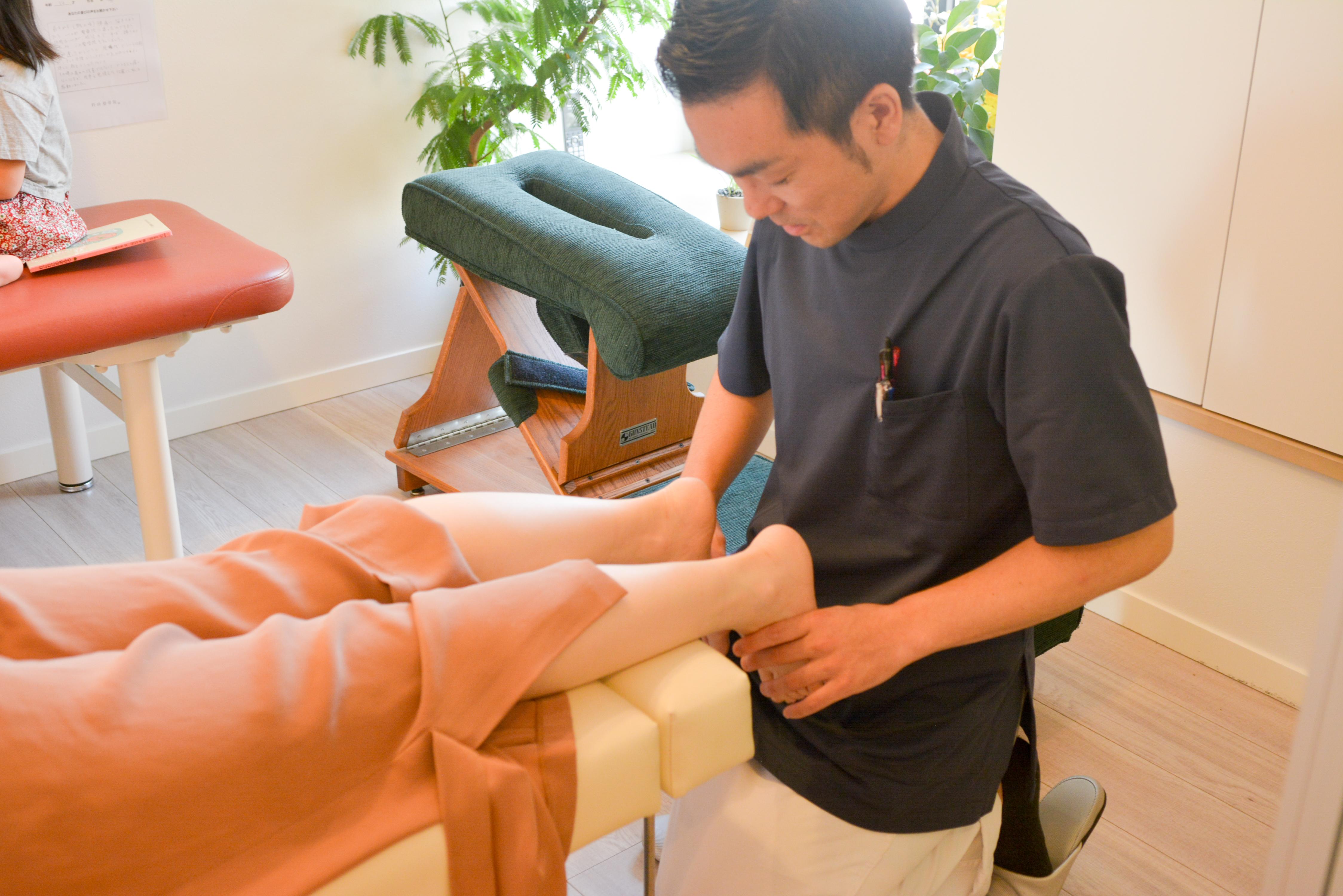 ベッドでうつ伏せの患者様の足の長さを左右比較している